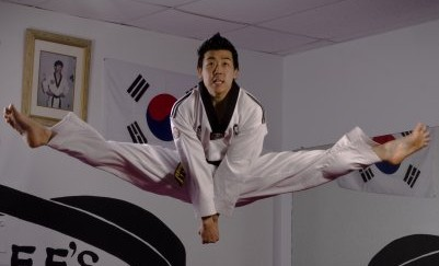 taekwondo black belt instructor doing a split jump kick
